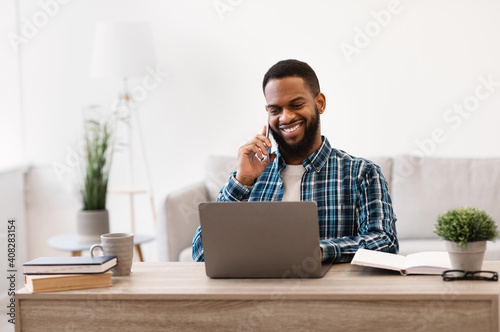 Obraz African Businessman Talking On Cellphone Sitting At Laptop In Office - fototapety do salonu