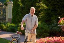 Portrait Of Mature Caucasian Man With His Bike. Summer Garden Background.