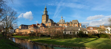 Panorama Cityscape Of Medieval Hanseatic City Zutphen In The Netherlands Against A Blue Sky With Clouds Lit Up By Afternoon Sun With Lush Winter Garden In The Foreground