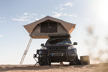 Rooftop Tent For Camping On The Roof Rack Of An Off-road SUV Car In A Desert