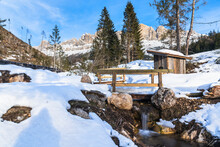 Small Woodend Bridge Over A Creek In A Snowy Mountain Landscape In The Dolomites On A Sunny Winter Day