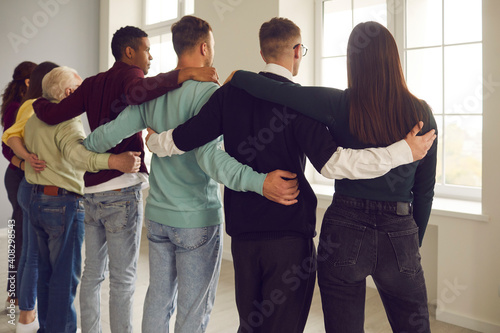 Obraz na plátně Group of diverse people stand in an embrace with their backs to the camera and look out the window