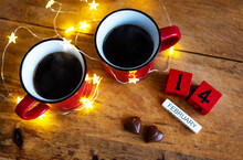 Two Cups Of Coffee In Red Cups On A Background Of Chocolate Canfet. Postcard With Date And Month. Valentine's Day Morning Surprise.