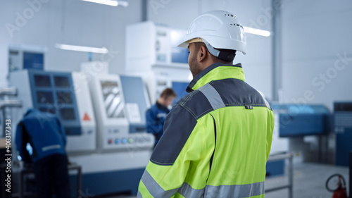 Valokuvatapetti Industry 4 Factory: Modern Worker Wearing Safety Jacket and Hard Hat, Walks Through Contemporary Industrial Workshop where Professionals are Working and Programming CNC Machinery