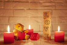 On A White Wooden Background A Teddy Bear With A Red Heart, Three Burning Red Candles, Wooden Cubes With The Word Love, In The Background A White Brick Wall