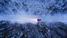 A Red Car Rides Along A Winter Road In The Night Forest. Snow On Trees And Roadsides, Aerial View.