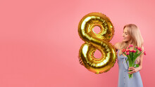 Carefree Young Lady With Golden Number Eight Balloon And Bunch Of Tulips Posing On Pink Background, Copy Space