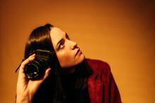 Chica Sujetando Cámara De Fotos Analógica Vintage Y Pelo Largo Moreno En Fondo De Estudio Naranja Elegante