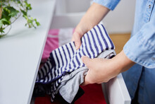 Close Up Of Woman Folding Up Clothes And Tidying Them Into Drawers