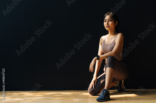 Obraz Focused young Asian sportswoman relaxing and getting ready for workout while crouching in studio on black background - full body length - fototapety do salonu