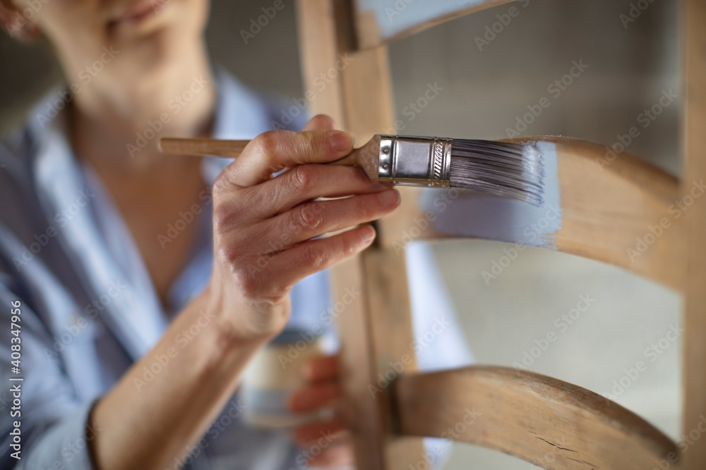 Fototapeta Close Up Of Woman Upcycling Furniture In Workshop At Home Painting Wooden Chair