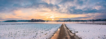 Landscape Panorama With Road, White Fields Cover By Snow And Sunset Sky.