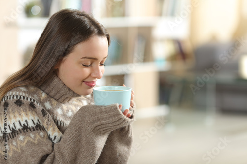 Relaxed teen smelling coffee in winter at home © PheelingsMedia