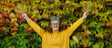 Senior Woman Standing Outdoors Against Colorful Natural Autumn Background, Stretching Arms.