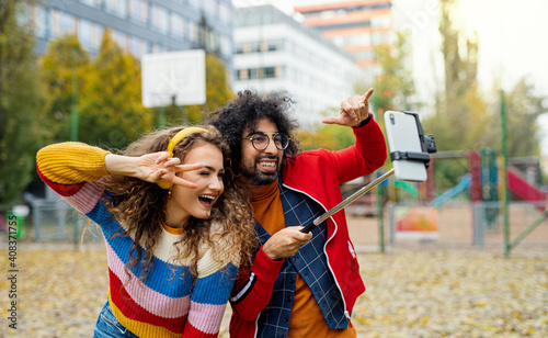 Fotografie, Obraz Young couple with smartphone making video for social media outdoors in park