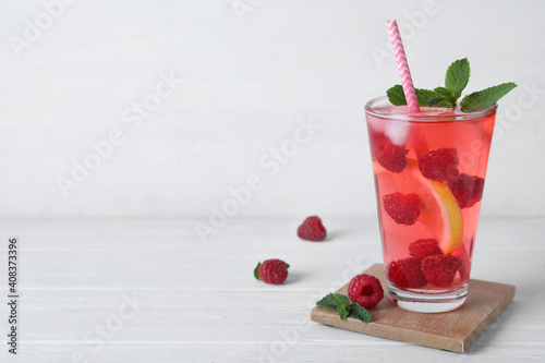 Delicious raspberry lemonade made with soda water and ingredients on white wooden table. Space for text © New Africa