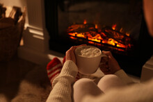 Woman Holding Drink Near Fireplace With Burning Woods Indoors, Closeup