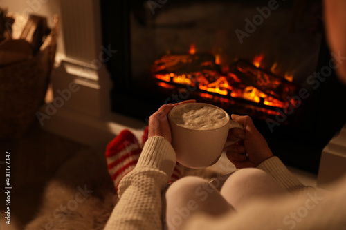 Woman holding drink near fireplace with burning woods indoors, closeup © New Africa