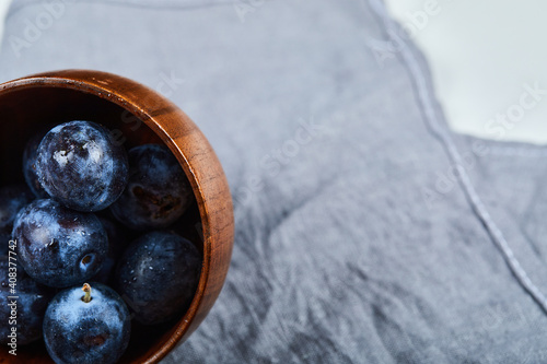 Photo Garden plums in a bowl on gray tablecloth