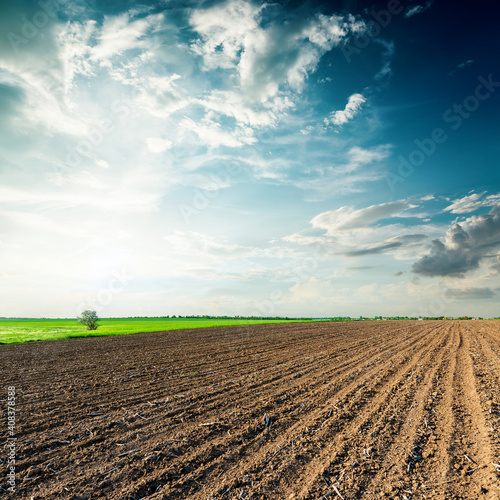Fotografie, Obraz black agriculture field and sunset in clouds