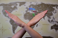 Two Crossed Hands In A Prohibitory Sign In Front Of A World Map With A Highly Blurred Background