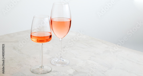 Rose wine in different glasses on light concrete background. Minimal Wine composition on white table. Long web banner with copy space. © Beton Studio
