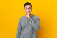 Young Caucasian Man Isolated On Yellow Background Showing A Sign Of Silence Gesture Putting Finger In Mouth