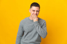 Young Caucasian Man Isolated On Yellow Background Happy And Smiling Covering Mouth With Hand