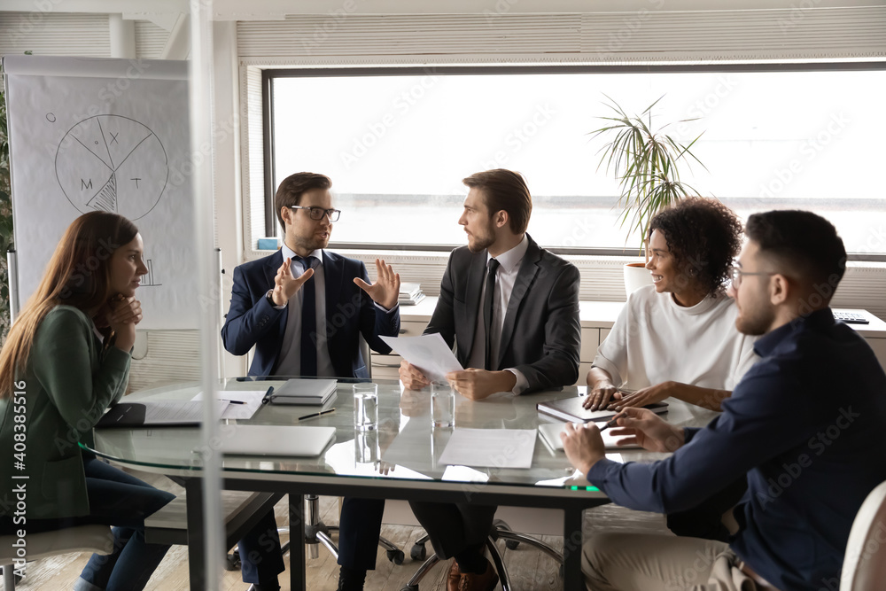 Fototapeta Diverse employees listening to colleague at meeting, sitting at table in boardroom, confident businessman sharing ideas with coworkers at briefing, business partners discussing project strategy