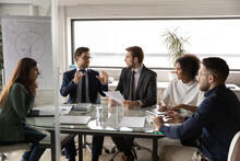 Diverse Employees Listening To Colleague At Meeting, Sitting At Table In Boardroom, Confident Businessman Sharing Ideas With Coworkers At Briefing, Business Partners Discussing Project Strategy