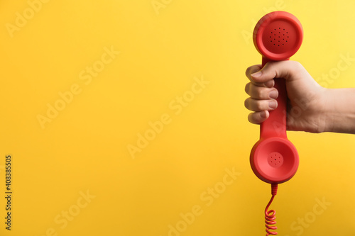 Closeup view of woman holding red corded telephone handset on yellow background, space for text. Hotline concept © New Africa