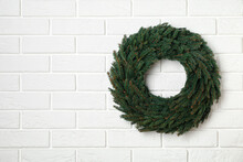 Christmas Wreath Made Of Fir Branches On White Brick Wall. Space For Text