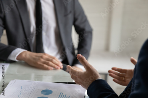 Canvas Print Close up two business partners discussing project statistics at meeting, sitting