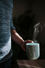 Man Holding Hot Cup Of Coffee While Standing At Home
