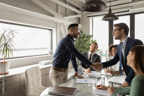 Fotografia Diverse business partners shaking hand in modern boardroom after negotiation, si