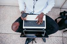 Man Having Coffee Sitting At Sidewalk While Working On Laptop