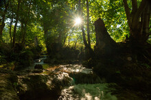 Waterfall Amidst Rocks On Sunny Day In Forest, ,Swabian Alb, Germany