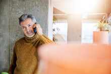 Mature Man Talking On Mobile Phone While Leaning On Pillar At Office