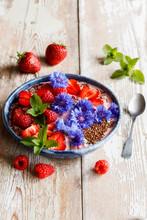 Plate Of Yogurt With Raspberries, Strawberries, Cornflowers And Mint