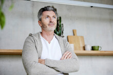 Mature Man Looking Away While Standing With Arms Crossed At Home