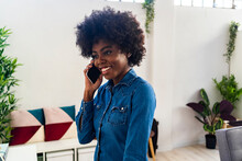 Young Woman Smiling While Talking On Mobile Phone At Home