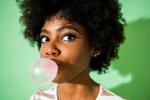 Young Woman Blowing Bubble Gum While Standing Against Green Background