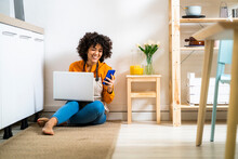 Young Woman With Laptop Using Mobile Phone While Sitting On Floor At Home