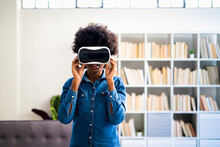 Woman Using Virtual Reality Headset While Standing At Home