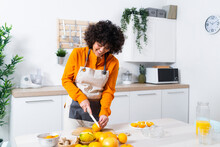 Woman Smiling While Cutting Orange Standing In Kitchen At Home