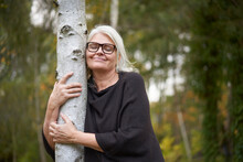 Smiling Senior Woman With Eyes Closed Embracing Tree Trunk In Public Park