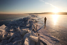 A Lone Figure Walks On The Ice Of A Frozen Lake. Dawn. Russia, Siberia, Baikal.
