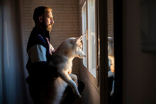 Male Pet Owner Holding Siberian Husky While Looking Through Window From Home
