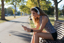 Smiling Young Woman Using Digital Tablet While Listening Music In Public Park On Sunny Day