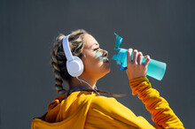 Young Athlete With Headphones Drinking Water While Standing Against Gray Wall